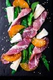 Salade avec le serrano de jamon de jambon, camembert, melon, arugula de plat en pierre noir d'ardoise sur le fond noir Vue supéri Photographie stock