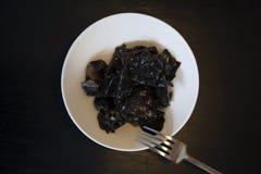 Salade avec les champignons noirs sur la table en bois noire Images stock