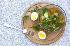 Salade avec les légumes frais et les herbes dans un bol en verre, oeufs à la coque Images libres de droits