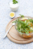 Salade avec les légumes frais et les herbes dans un bol en verre sur un conseil en bois, les oeufs à la coque et le yogur Photos stock