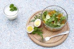 Salade avec les légumes frais et les herbes dans un bol en verre sur un conseil en bois, les oeufs à la coque et le yogur Images stock