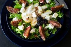 Salade avec les poires, la laitue, les figues, les noix, le fromage de chèvre, les noix et le miel images libres de droits
