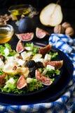 Salade avec les poires, la laitue, les figues, les noix, le fromage de chèvre, les noix et le miel photos libres de droits