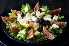 Salade avec les poires, la laitue, les figues, les noix, le fromage de chèvre, les noix et le miel photographie stock