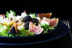 Salade avec les poires, la laitue, les figues, les noix, le fromage de chèvre, les noix et le miel photos stock