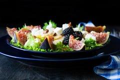 Salade avec les poires, la laitue, les figues, les noix, le fromage de chèvre, les noix et le miel image stock