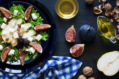 Salade avec les poires, la laitue, les figues, les noix, le fromage de chèvre, les noix et le miel photo stock
