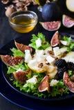 Salade avec les poires, la laitue, les figues, les noix, le fromage de chèvre, les noix et le miel image libre de droits