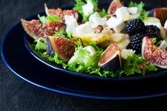 Salade avec les poires, la laitue, les figues, les noix, le fromage de chèvre, les noix et le miel photo libre de droits
