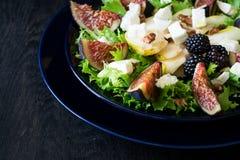 Salade avec les poires, la laitue, les figues, les noix, le fromage de chèvre, les noix et le miel images stock