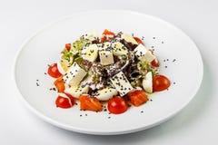 Salade avec les poissons rouges avec de la sauce blanche du plat rond sur le CCB blanc image stock
