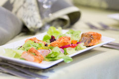 Salade avec les saumons rouges de poissons se trouvant d'un plat Photos stock