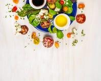 Salade avec les tomates, le feta, le vinaigrette balsamique de mustart et la variation de verts, du plat bleu photos stock