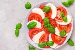 Salade caprese avec les tomates et le fromage mûrs de mozzarella, feuilles fraîches de basilic sur le fond concret Nourriture ita photo stock