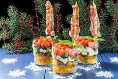 Salade caprese de fête avec le lard frit sur des brochettes en verres Photographie stock