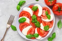 Salade caprese italienne fraîche avec les tomates, le fromage de mozzarella, le basilic, l'huile d'olive et la fourchette coupés  image stock