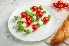 Salade Caprese - kebab met tomaat, mozarella en basilicum, tomaten en Franse baguette, Italiaanse keuken en gezonde vegetar stock afbeelding