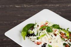 Salade classique traditionnelle de Shopska avec des tomates, des poivrons, des concombres et le fromage dans le plat blanc sur la Photos stock