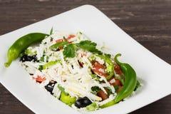 Salade classique traditionnelle de Shopska avec des tomates, des poivrons, des concombres et le fromage dans le plat blanc sur la Images libres de droits