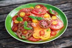 Salade colorée de tomate avec l'héritage, en forme de poire, coeur de boeuf, tigerella, brandywine, cerise, tomates noires en ver photo stock