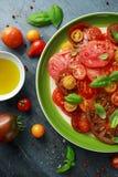 Salade colorée de tomate avec l'héritage, en forme de poire, coeur de boeuf, tigerella, brandywine, cerise, tomates noires en ver image stock