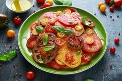 Salade colorée de tomate avec l'héritage, en forme de poire, coeur de boeuf, tigerella, brandywine, cerise, tomates noires en ver photos stock