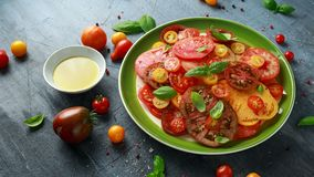 Salade colorée de tomate avec l'héritage, en forme de poire, coeur de boeuf, tigerella, brandywine, cerise, tomates noires en ver image libre de droits