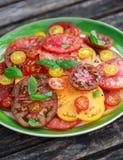 Salade colorée de tomate avec l'héritage, en forme de poire, coeur de boeuf, tigerella, brandywine, cerise, tomates noires en ver photographie stock libre de droits