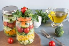 Salade colorée faite maison saine végétale dans le pot de maçon avec la tomate, laitue, brocoli sur le bleu Déjeuner pour le trav Image libre de droits