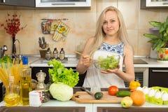 Salade coocking de femme à la table de cuisine Photographie stock libre de droits