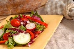 Salade croquante d'une plaque jaune avec du pain rustique Photographie stock