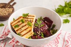 Salade cuite au four de betterave avec le persil et le pétrole grillés de tofu en BO blanche photographie stock