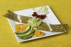 Salade décorée d'asperge au-dessus d'un fond jaune photographie stock libre de droits