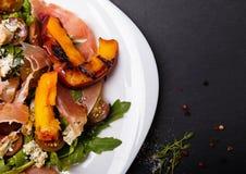 Salade délicieuse avec les pêches et le prosciutto grillés Photo stock