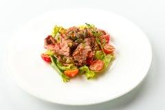 Salade délicieuse de viande verte avec le bifteck juteux rôti, la tomate et la sauce verte dans un plat blanc d'isolement sur le  photographie stock