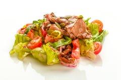 Salade délicieuse de viande verte avec le bifteck juteux rôti, la tomate et la sauce verte dans un plat blanc d'isolement sur le  image stock