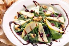 Salade d'épinards avec la poire, les noix et le fromage bleu Images stock