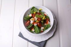 Salade d'épinards avec les tomates-cerises et le maïs dans la cuvette, table en bois blanche Images stock