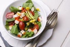 Salade d'épinards avec les tomates-cerises et le maïs dans la cuvette, table en bois blanche Photographie stock