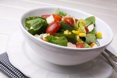 Salade d'épinards avec les tomates-cerises et le maïs dans la cuvette, table en bois blanche Photos stock