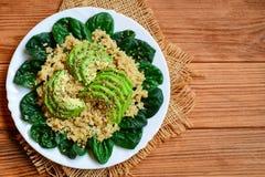 Salade d'épinards d'avocat de quinoa Salade simple de quinoa avec les tranches fraîches d'épinards et d'avocat d'un plat servi Fo Images stock