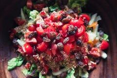 Salade d'été avec les graines et la sultanine de tomates dans une cuvette en bois Image stock