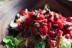 Salade d'été avec les graines et la sultanine de tomates dans une cuvette en bois Photographie stock libre de droits