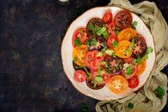 Salade d'été des tomates de différentes couleurs avec les herbes et le poivre verts Photographie stock