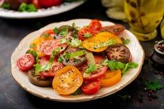 Salade d'été des tomates de différentes couleurs avec les herbes vertes Image libre de droits