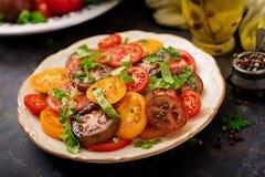 Salade d'été des tomates de différentes couleurs avec les herbes vertes Images stock