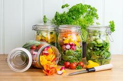 Salade dans des pots en verre de stockage Contenu un de renversement image stock