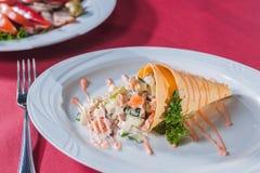 Salade dans un cône de gaufre avec de la sauce d'un plat blanc Photos stock