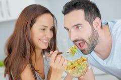 Salade de alimentation de Madame dans la bouche du ` s de l'homme Photographie stock