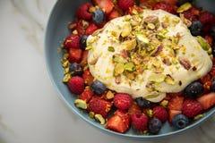 Salade de baie avec des fraises, des myrtilles, la framboise, la pistache, le zeste de citron et la crème de quark d'huile de lin photos libres de droits